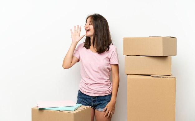Молодая девушка движется в новом доме среди коробок, крича с широко открытым ртом