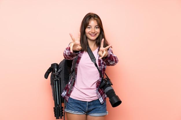 笑顔と勝利のサインを示す分離のピンクの壁の上の若い写真家の女の子