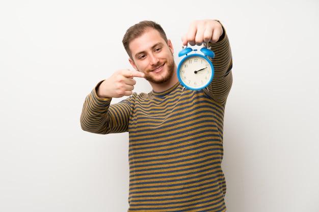 ビンテージの目覚まし時計を保持している孤立した白い壁の上のハンサムな男