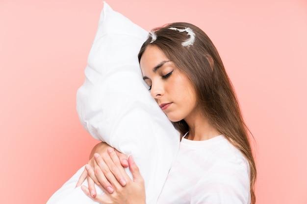 孤立したピンクの壁の上のパジャマの若い女性