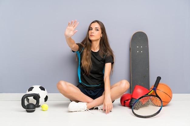 Молодая спортивная женщина сидит на полу, делая остановки жест рукой