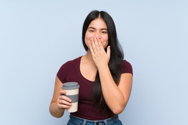 Девушка молодого подростка азиатская держа кофе взятия прочь с выражением лица сюрприза