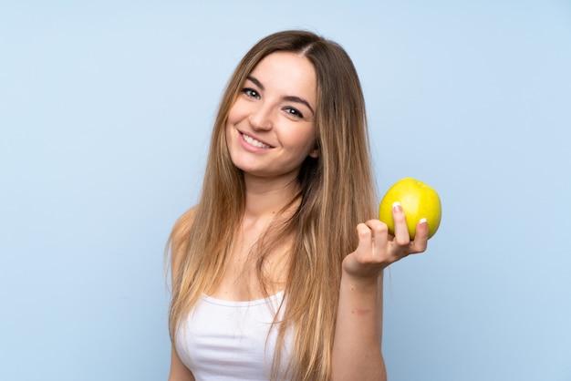 リンゴと分離の青い壁の上の若い女性