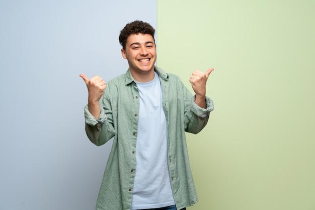両方の手でジェスチャーを親指を与えると笑顔の青と緑の壁の上の若い男
