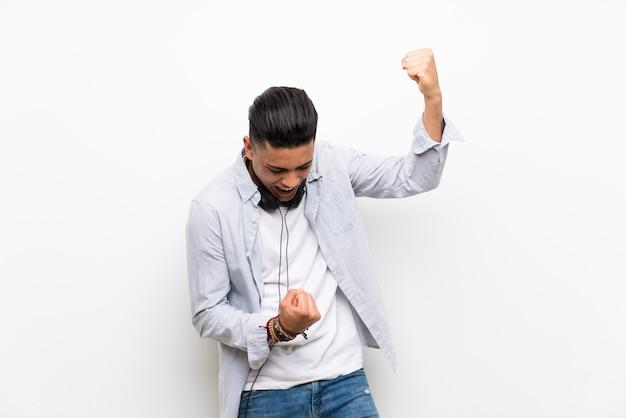勝利を祝うイヤホンで孤立した白い壁の上の若い男