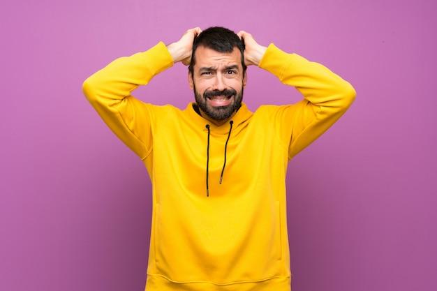 黄色のスウェットシャツでハンサムな男はイライラし、頭に手を取ります