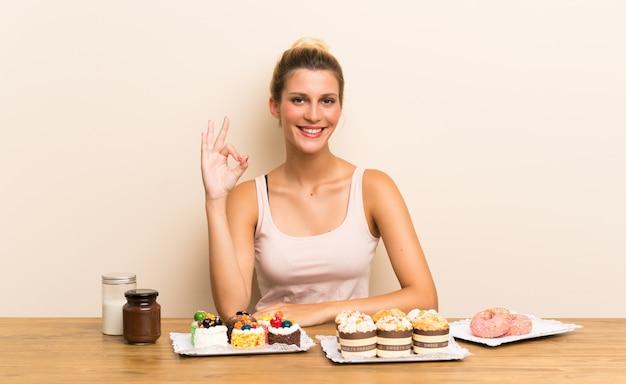 Молодая женщина с большим количеством различных мини-пирожных в таблице показывает знак ок с пальцами