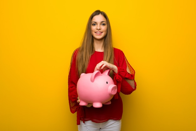 Молодая девушка с красным платьем над желтой стеной берет копилку и счастлива, потому что она полна