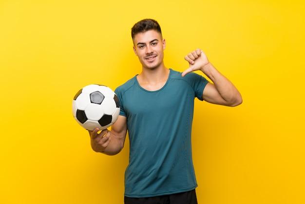 孤立した黄色の壁を越えて誇りと自己満足のハンサムな若いフットボール選手男
