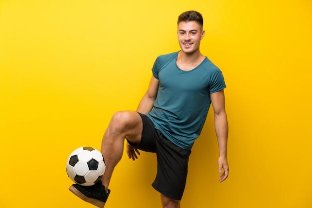孤立した黄色の壁の上のハンサムな若いフットボール選手男