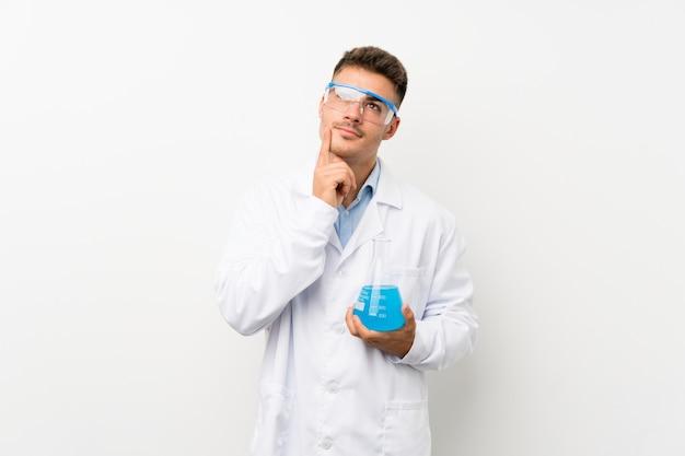 アイデアを考えて孤立した壁の上の若い科学持株実験室のフラスコ
