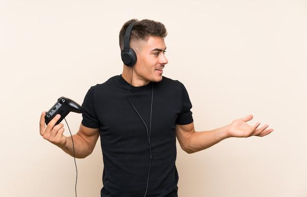 驚きの表情で孤立した壁を越えてビデオゲームコントローラーで遊ぶ若いハンサムな男