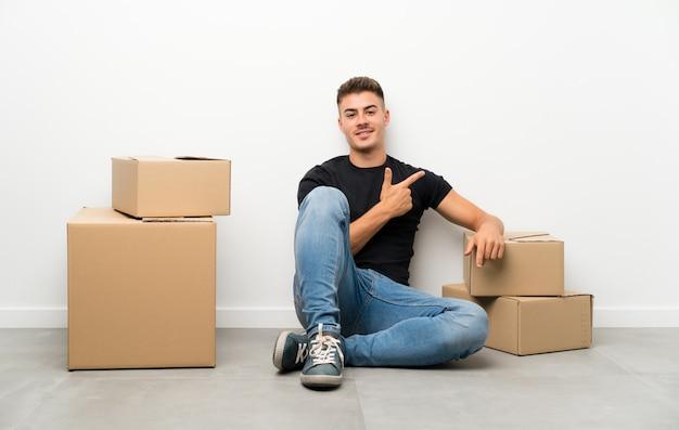 ハンサムな若い男が側に指を指しているボックスの間で新しい家に移動