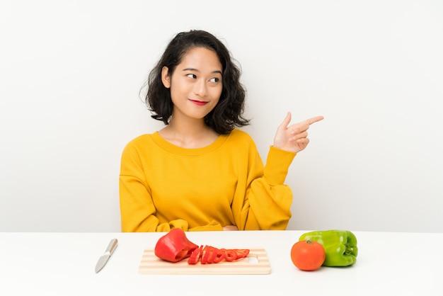 側に指を指しているテーブルで野菜を持つ若いアジアの女の子