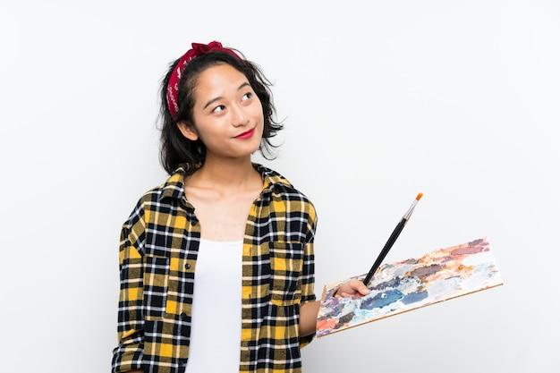 笑顔ながら見上げる孤立した白い壁にパレットを保持している若いアーティストの女性
