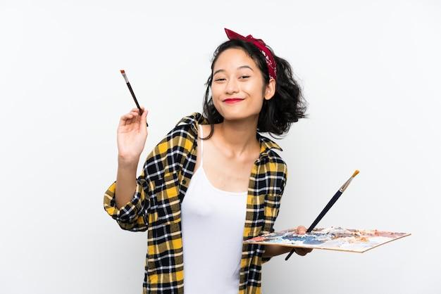 孤立した白い壁にパレットを保持している若いアーティストの女性