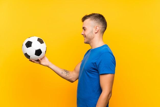 幸せな表情で孤立した黄色の壁にサッカーボールを置く若いハンサムな金髪男