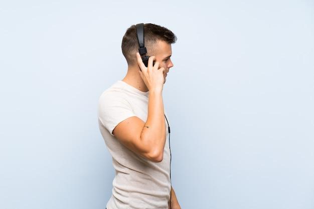 ヘッドフォンで音楽を聴く孤立した青い壁の上の若いハンサムな金髪男