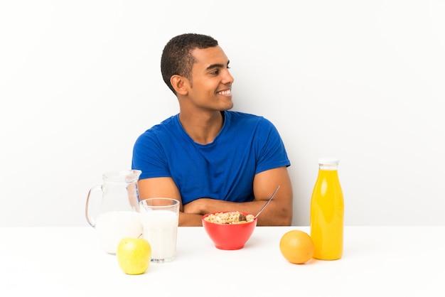 側にいるテーブルで朝食を持っている若い男