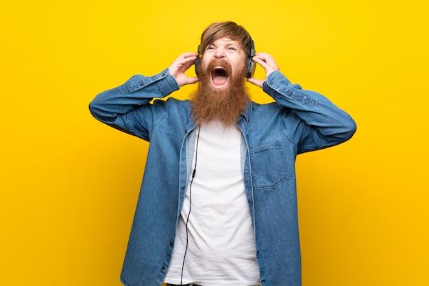 Рыжий мужчина с длинной бородой над изолированной желтой стеной, слушая музыку в наушниках