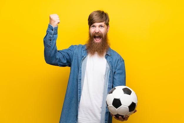 サッカーボールを保持している孤立した黄色の壁の上の長いひげを持つ赤毛の男