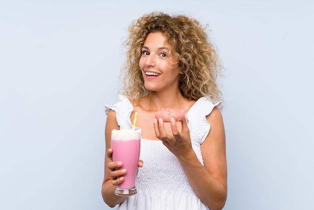 いちごのミルクセーキとドーナツを保持している巻き毛の若いブロンドの女性