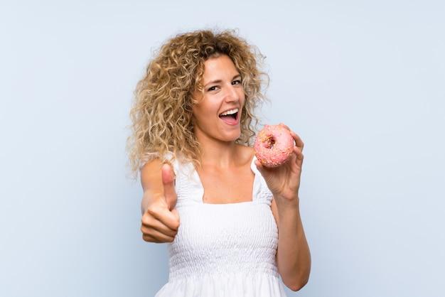 何か良いことが起こったので親指で孤立した青い壁にドーナツを保持している巻き毛の若いブロンドの女性