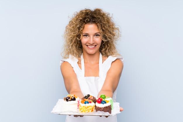 たくさんの異なるミニケーキを保持している巻き毛の若いブロンドの女性