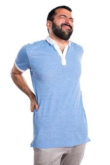背中の痛みと青のシャツを持つ男