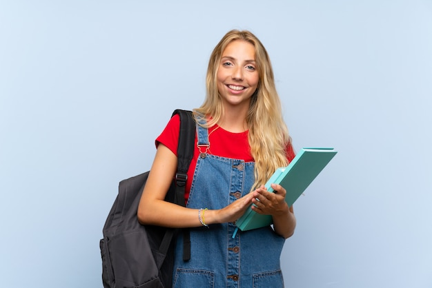 拍手分離の青い壁の上の若い金髪の学生女性