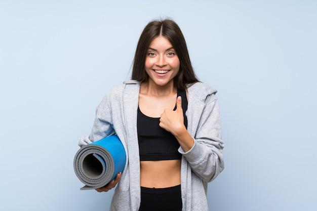 驚きの表情で孤立した青い壁の上のマットを持つ若いスポーツ少女