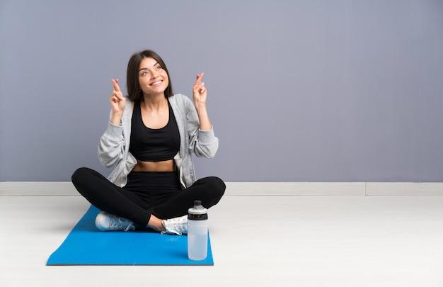 指を交差でマットで床に座っている若いスポーツ女性