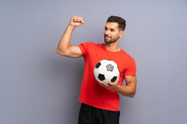 勝利を祝う孤立した白い壁の上のハンサムな若いフットボール選手男