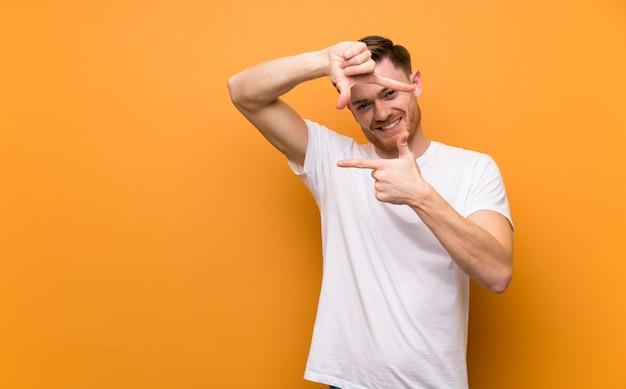 Рыжий человек над коричневой стены фокусировки лицо. обрамление символ