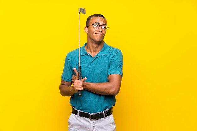 Афро-американский игрок в гольф человек сомневается жест, поднимая плечи