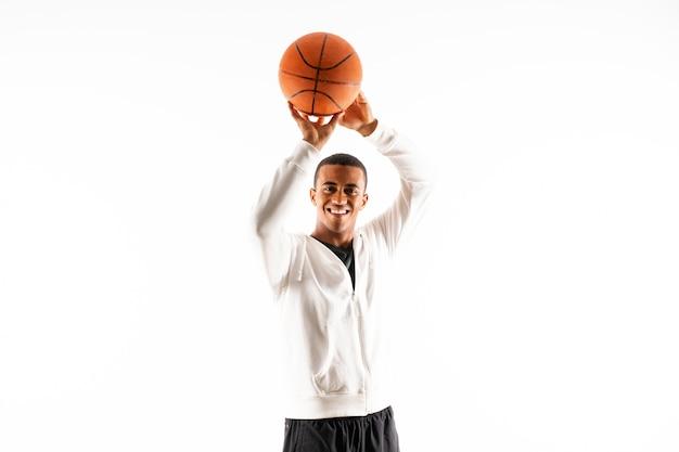 孤立した白い壁の上のアフロアメリカンバスケットボールプレーヤー男