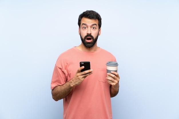 Молодой человек с бородой, держа прочь кофе на изолированной синей стене удивлен и отправив сообщение
