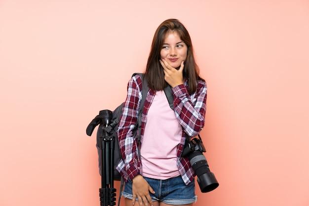 Молодая девушка фотографа над изолированной розовой стеной думая идея