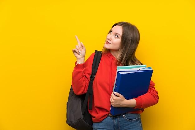 人差し指で素晴らしいアイデアを指している黄色の壁の上のティーンエイジャーの学生の女の子