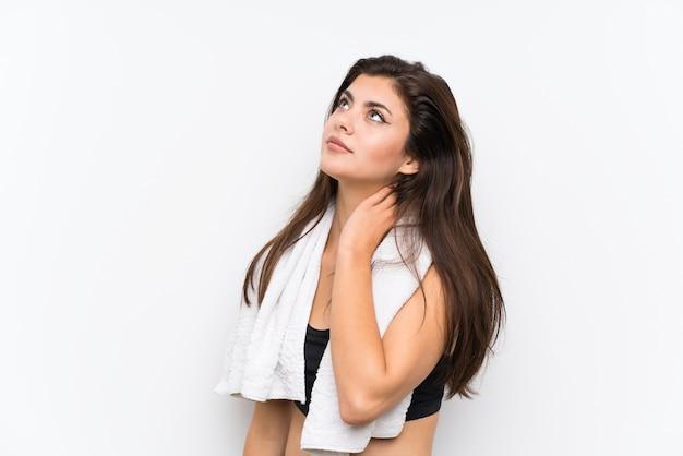 Девушка спорта подростка над изолированной белой стеной стоя и думая идея