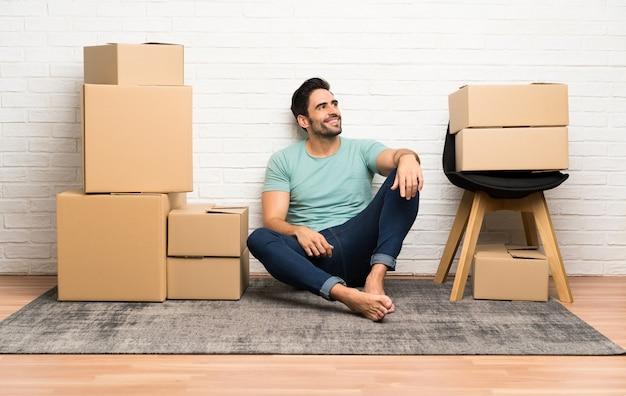 笑って見上げるボックスの間で新しい家に移動するハンサムな若い男