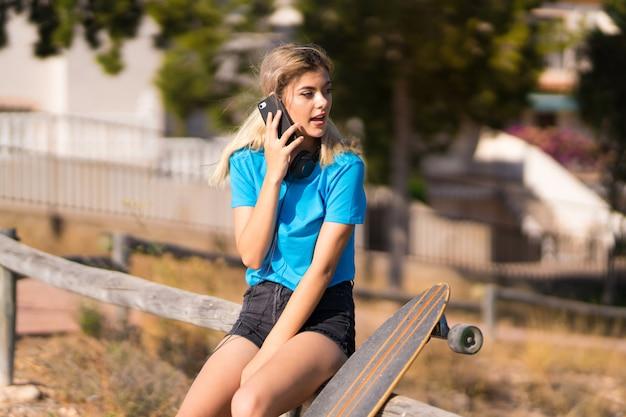 携帯電話との会話を維持する屋外でスケートを持つティーンエイジャーの女の子