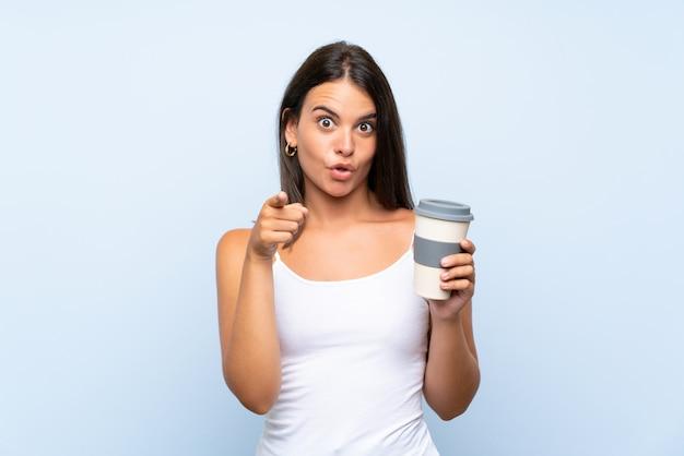 Молодая женщина, держащая прочь кофе на изолированной синей стене удивлен и указывая фронт