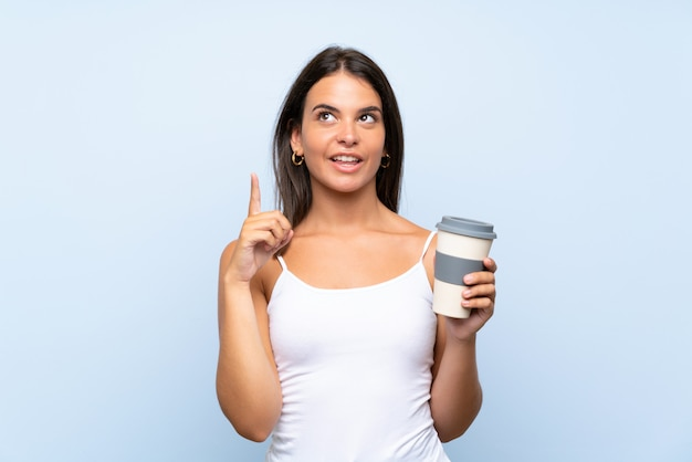 Молодая женщина, держащая кофе на вынос на изолированной синей стене, намереваясь реализовать решение, поднимая палец вверх