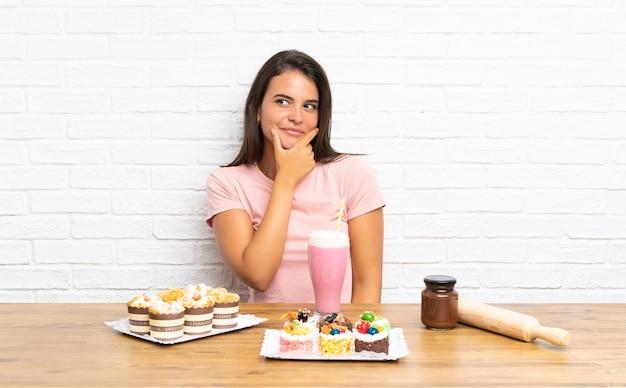Молодая девушка с большим количеством различных мини-тортов, думая, идея