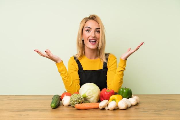 Молодая блондинка с большим количеством овощей несчастна и разочарована чем-то