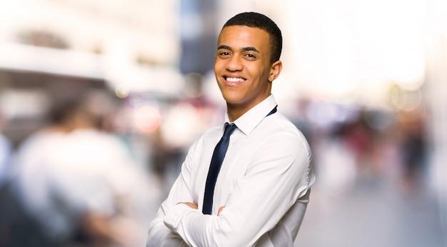 街で笑顔で肩越しに見ている若いアフロアメリカ人実業家