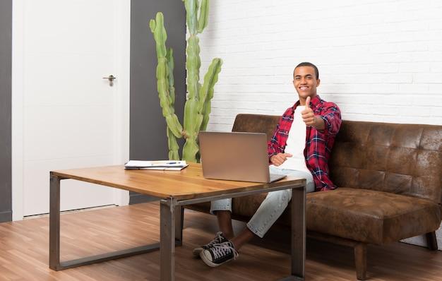Афро-американский мужчина с ноутбуком в гостиной, давая пальцы вверх жест, потому что случилось что-то хорошее