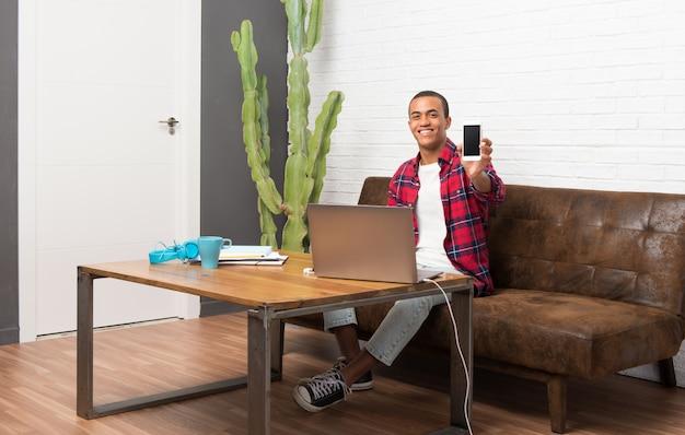 Афро-американский мужчина с ноутбуком в гостиной смотрит в камеру и улыбается во время использования мобильного телефона
