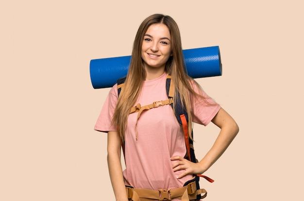 Молодая женщина рюкзаком позирует с руки на бедре и улыбается на желтой стене
